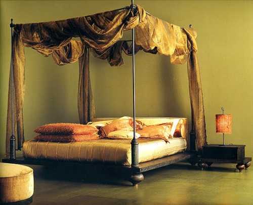 Wooden four-poster beds in the bedroom with extravagant curtains