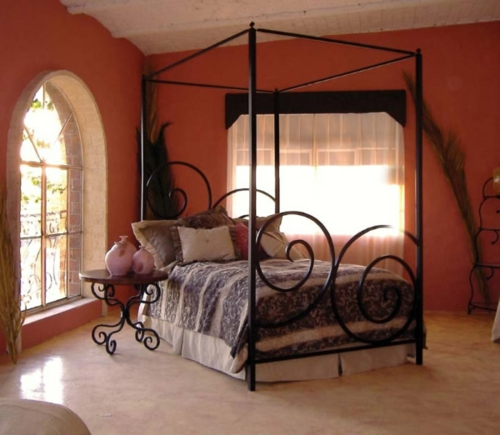 Wooden four-poster beds in bedroom frame metal bent