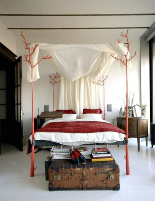 Wooden four-poster beds in the bedroom red bedding pillows