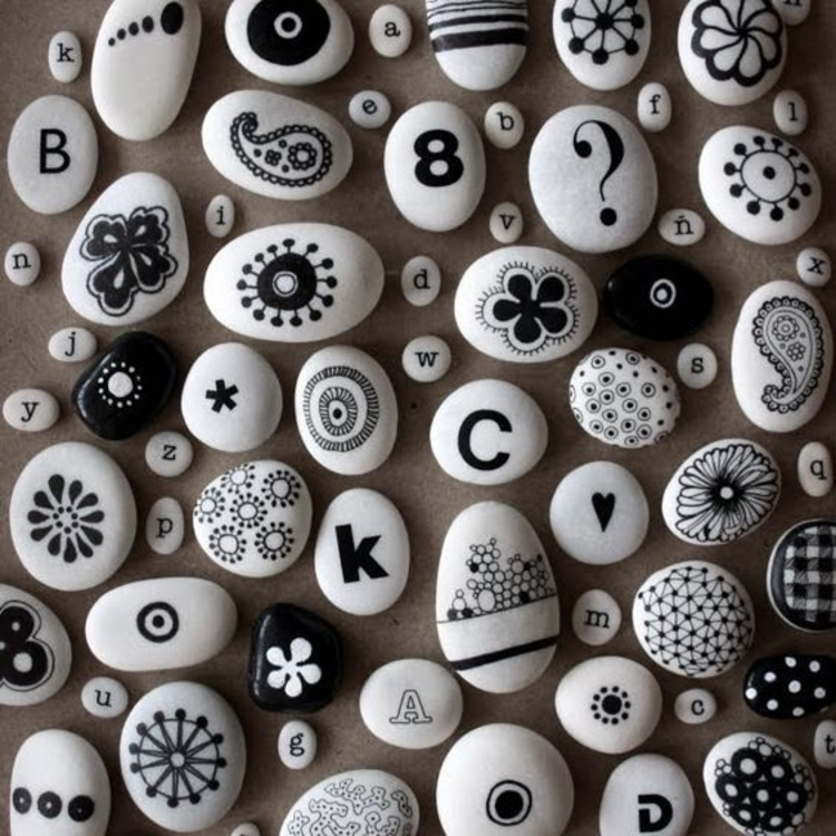 Stones painted black motifs flowers and letters painted stones