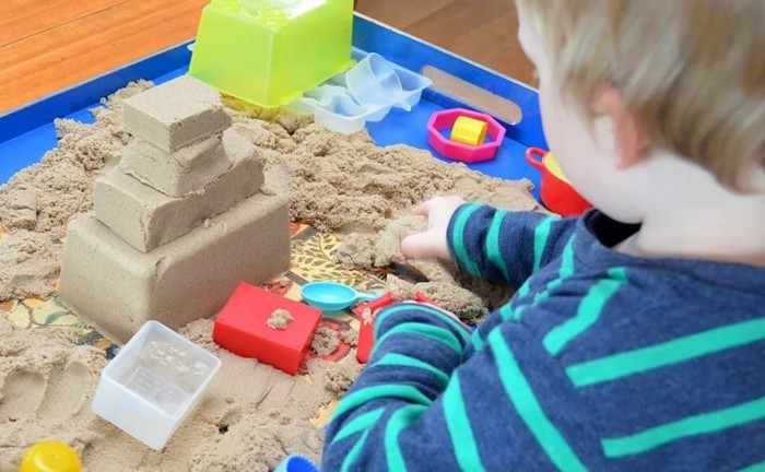 child play with kinetic sand to make yourself