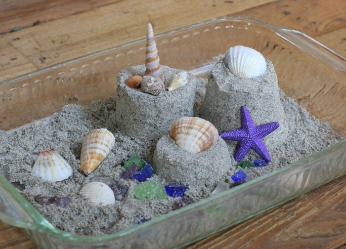Kinetic sand in the casserole dish with mussels and snails