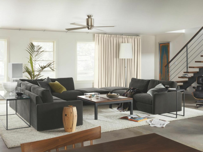modern living room set up black sofas light carpet plant